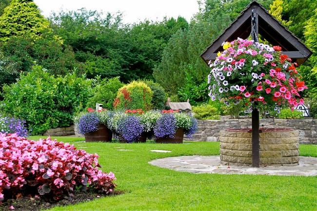 Если на дачном участке не хватает места для полноценного цветника, можно организовать небольшую клумбу прямо под окнами, возле крыльца, вдоль дорожек и даже… на фонарном столбе. Так вы решите проблему нехватки свободных метров, и заодно акцентируете входную зону. Для вашего вдохновения мы собрали фотографии — идеи для клумбы или небольших цветников во дворе и на «пятачке» возле дома. Виды клумб возле дома своими руками По способу обустройства и форме клумбы разделяются на несколько основных видов: • миксбордеры – клумбы смешанного типа, свободной формы и ширины. Обычно это засаженная цветами полоса вдоль изгороди, стены дома или садовой дорожки; • модульные клумбы – более сложный вид оформления цветника, который включает в себя не только растения, но и декоративное мощение и малые архитектурные формы; • солитер – клумба, на которой у всех растений имеется какой-либо общий признак: цвет, высота, форма листвы. Обычно такой цветник располагают отдельно – в таком месте, где его будет хорошо видно; • бордюр – клумба-полоса шириной не более 50 см. Высаживают в таких цветниках небольшие плотно растущие цветы. Хорошо использовать бордюры для отделения одних элементов сложной клумбы от других; • рокарий – гармоничное сочетание камней и растений в цветнике. Можно встретить более простое название такой клумбы – каменный сад; • рабатка – низкая длинная грядка с цветами. Её редко используют саму по себе, чаще как составляющую часть большой клумбы; • альпинарий – цветник, основу которого составляют растения альпийской и субальпийской флоры. Выбор подходящего места для создания клумбы Прежде чем приступить к выполнению цветочных композиций, рекомендуется начертить и разметить проект на бумаге. Форма конструкции подбирается в зависимости от стиля постройки и окружающего ландшафта. Участок выбирается так, чтобы растения получали освещение не менее пяти часов в день. Лучше выбрать солнечное место без сквозняков. С выбранного участка убирается газонная трава и сорняки. Размеры создани
